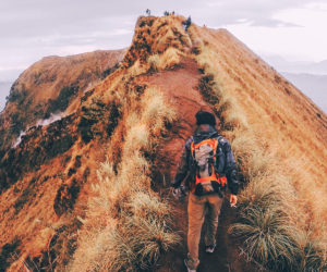 Young Man climbing a hill by an ocean