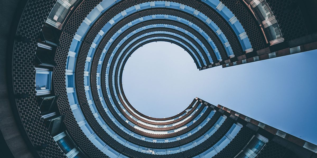 looking straight up at a c curved corporate building